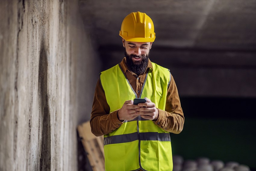 A smiling construction worker wearing a high-vis yellow jacket looking at a mobile phone.