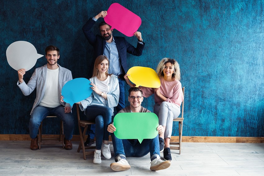 Five people sitting down smiling and holding cardboard cut outs of speech bubbles.